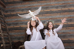 Two girls in wreaths and white dress releasing a white dove as it flies away