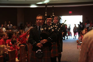 Three bagpipers in scottish kilt uniform marching down the aisle during a celebration of life.
