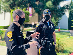 Two male motor escort officers in black uniform having a conversation.