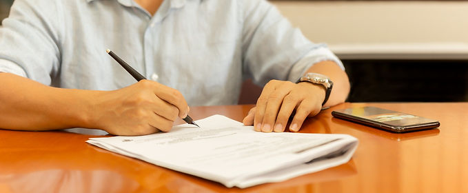 man-signing-documents-with-quill-pen-on-wooden-desk_edited.jpg