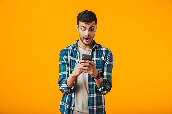surprised-young-man-wearing-plaid-shirt-standing-isolated-over-orange-wall-using-mobile-ph