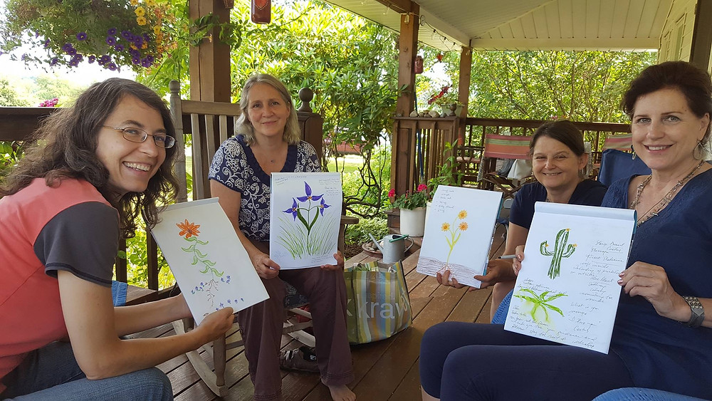 Four women searing on a porch holding up their drawings of plants.