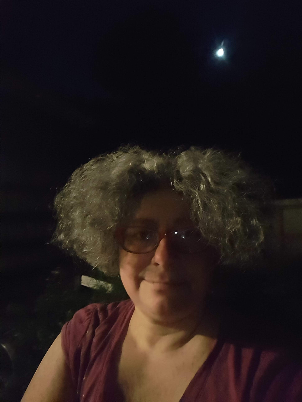 Selfie of woman outside in fenced yard at night with Traveler moon in background.