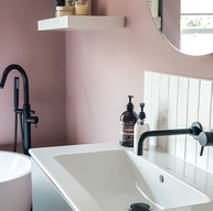 Adding a warm colour to the walls to make an otherwise monochrome bathroom welcoming