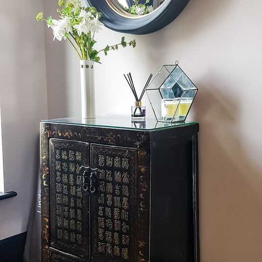 Antique chinese cabinet with round mirror in entrance hall