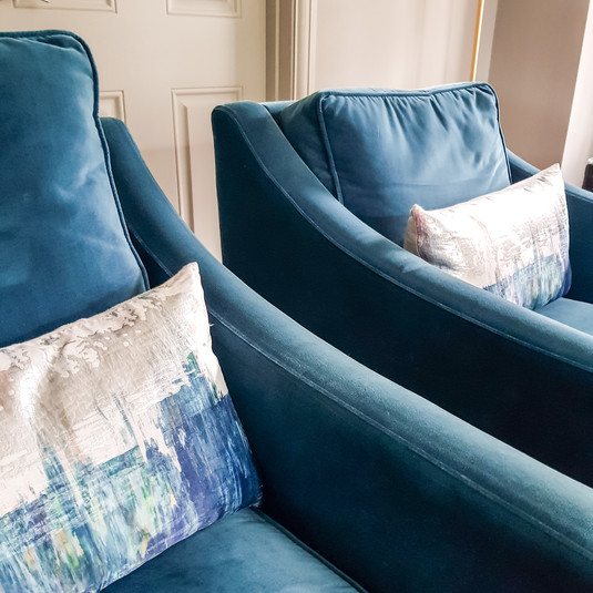 Colourful armchairs add interest to a neutral space