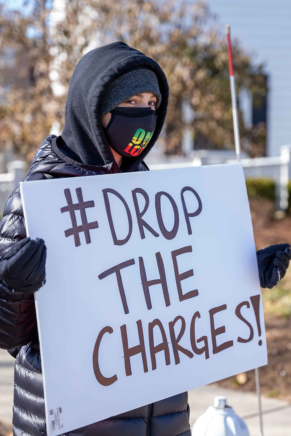"""A protester poses for a photograph while holding a protest sign saying """"#DropTheCharges!"""" and standing in solidarity with Nick Haas, while outside the Ramsey Borough Hall on Sunday, Jan.24th, 2021. (Photo/Julian Leshay)"""