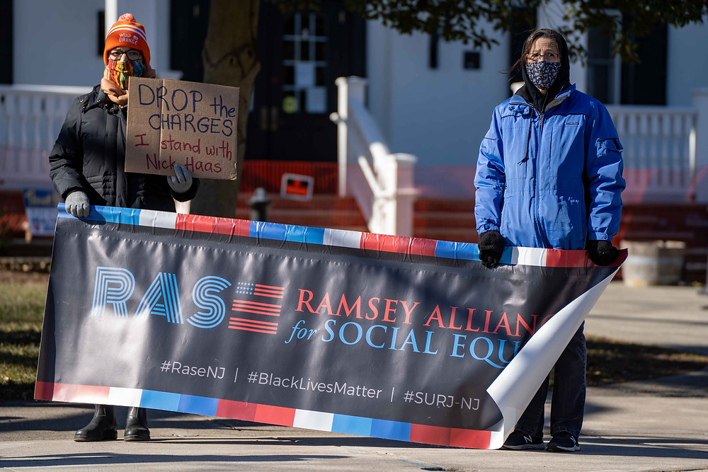 """Two protesters hold a Ramsey Alliance for Social Equity banner and a sign saying """"Drop The Charges I Stand With Nick Haas"""" outside the Ramsey Borough Hall on Sunday, Jan. 24th, 2021. (Photo/Julian Leshay)"""