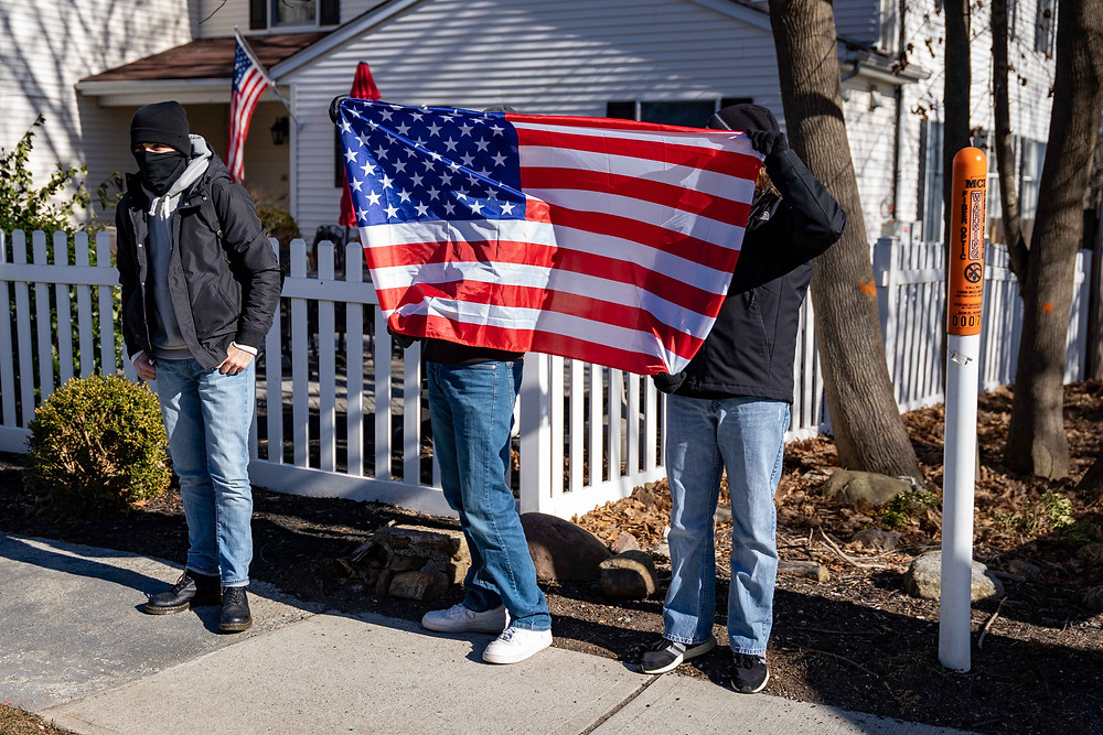 A group of three individuals, two hiding behind the American flag, counter-protesting the RASE organization and their stance on Ramsey Police Department across the street from  the Ramsey Borough Hall on Sunday, Jan. 24th, 2021. (Photo/Julian Leshay)