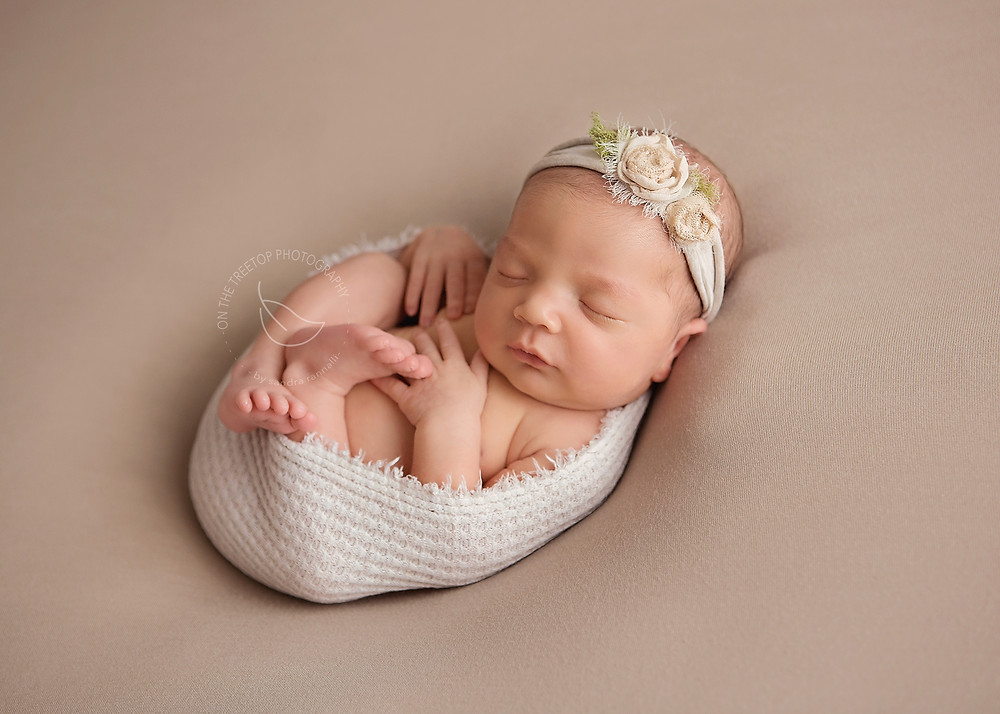 newborn girl posed on bean bag curled on her back and swaddled in soft textured wrap