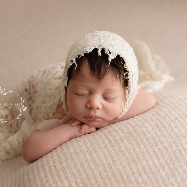 beautiful  newborn photographed on cream in a vintage bonnet