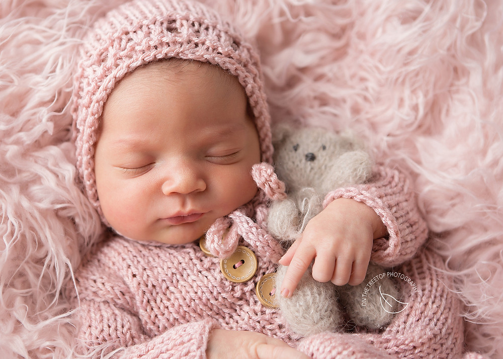 precious newborn girl in hand knit pink romper curled on pink fur