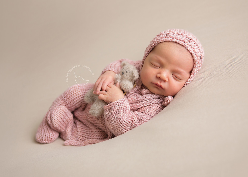 newborn girl posed on beanbag with hand knit teddy bear