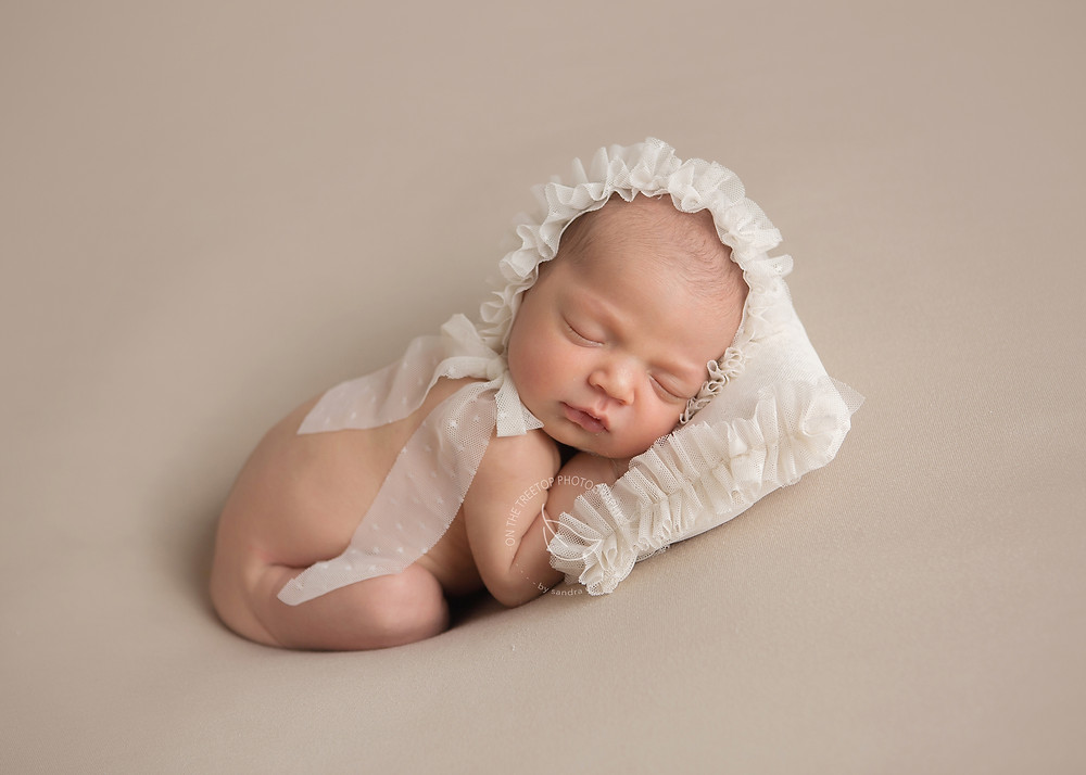 newborn girl posed on beanbag with custom lace pillow and matching ruffle bonnet
