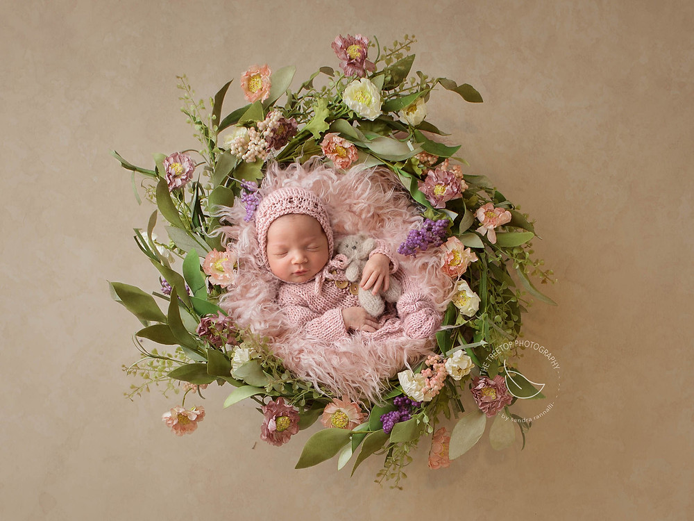 newborn girl curled in pink fur inside a floral wreath