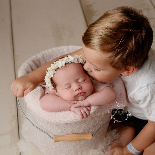 newborn photographed in a bucket with big brother