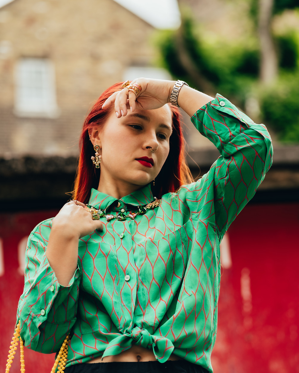 Red head woman in a green shirt holding her hand to her forehead looking down.