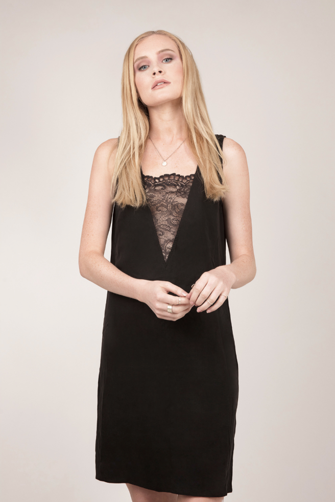Blond model facing the camera wearing a black slip dress with a lace panel