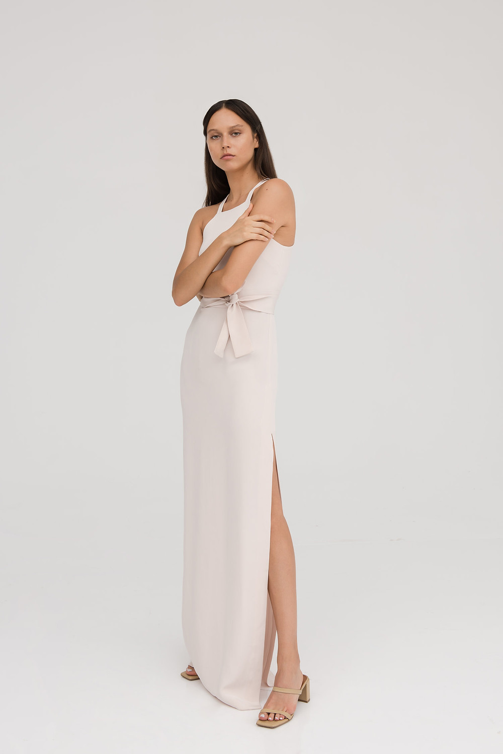 Female model in a white strap full length dress looking at the camera