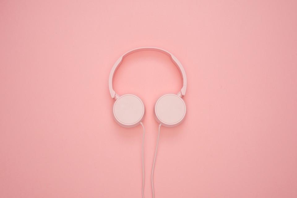 Pastel pink headphones against a slightly darker pink background