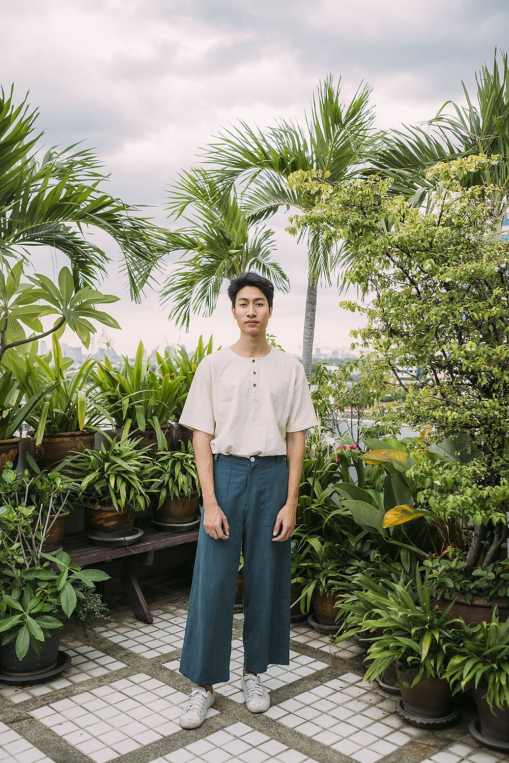 A guy standing against a green back drop of plants wearing green trousers and a white t-shirt tucked in