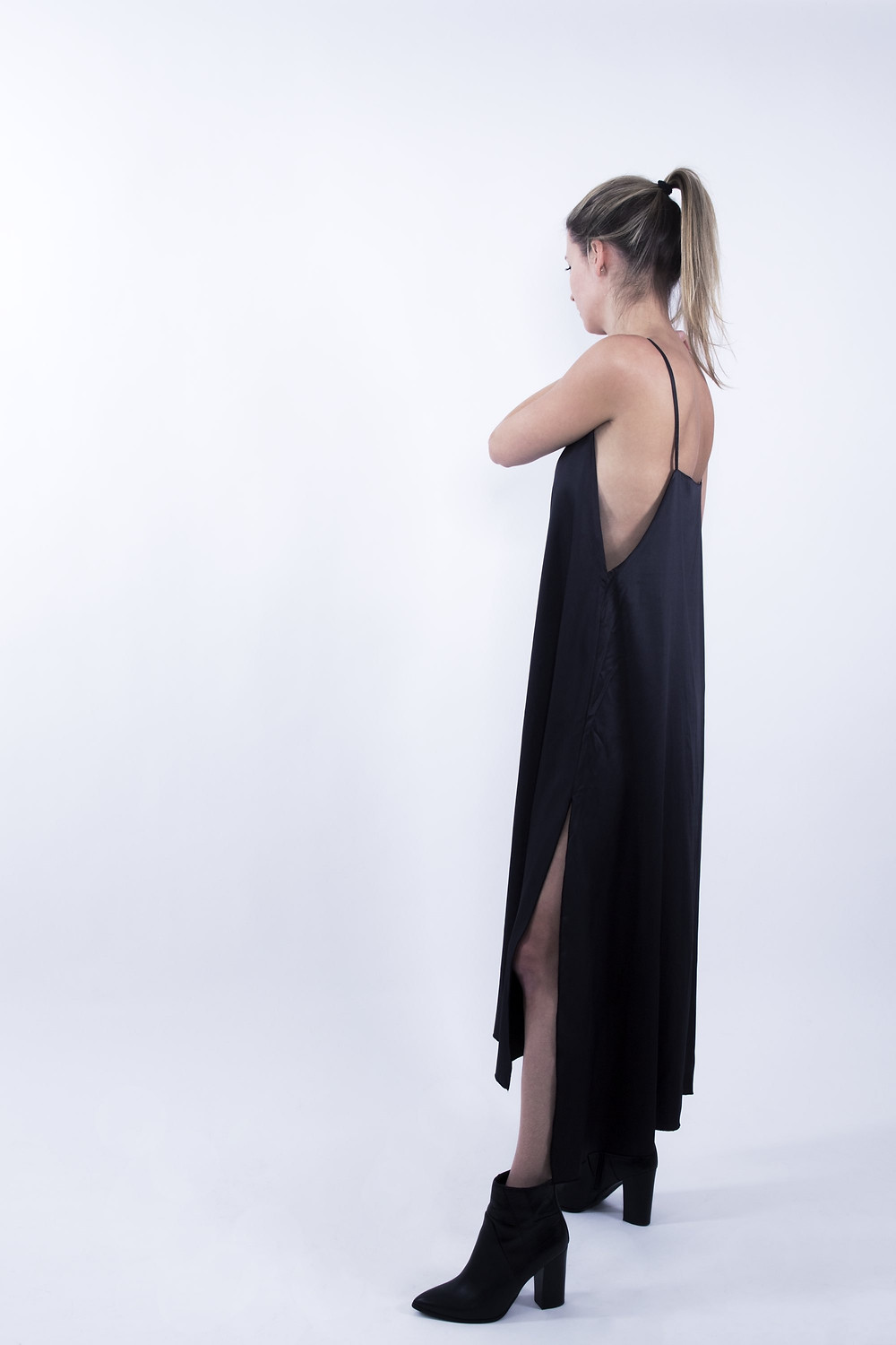 Model facing away from the camera wearing a black slip dress with a split on the side