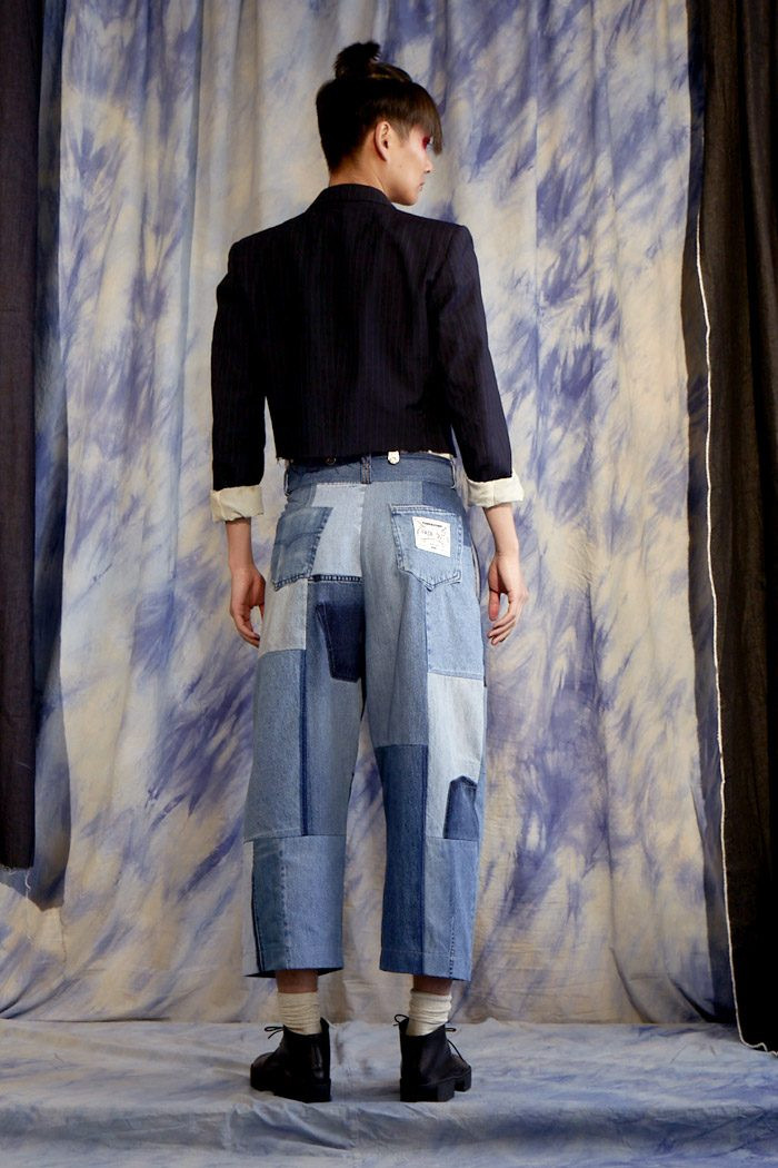 A model standing with their back in upcycled jeans and a black blazer