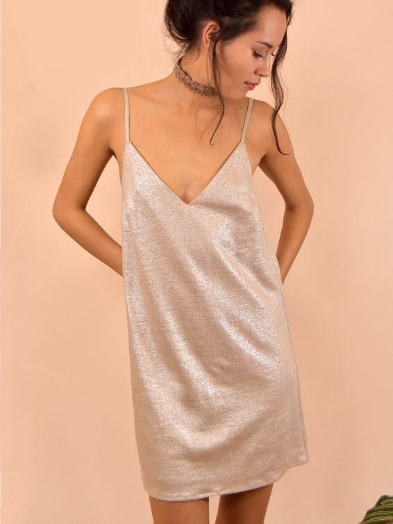 model facing away from the camera dressed in a golden slip dress