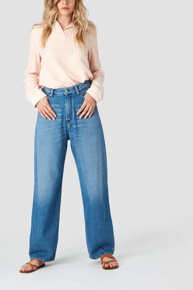 A girl in blue jeans and pink shirt