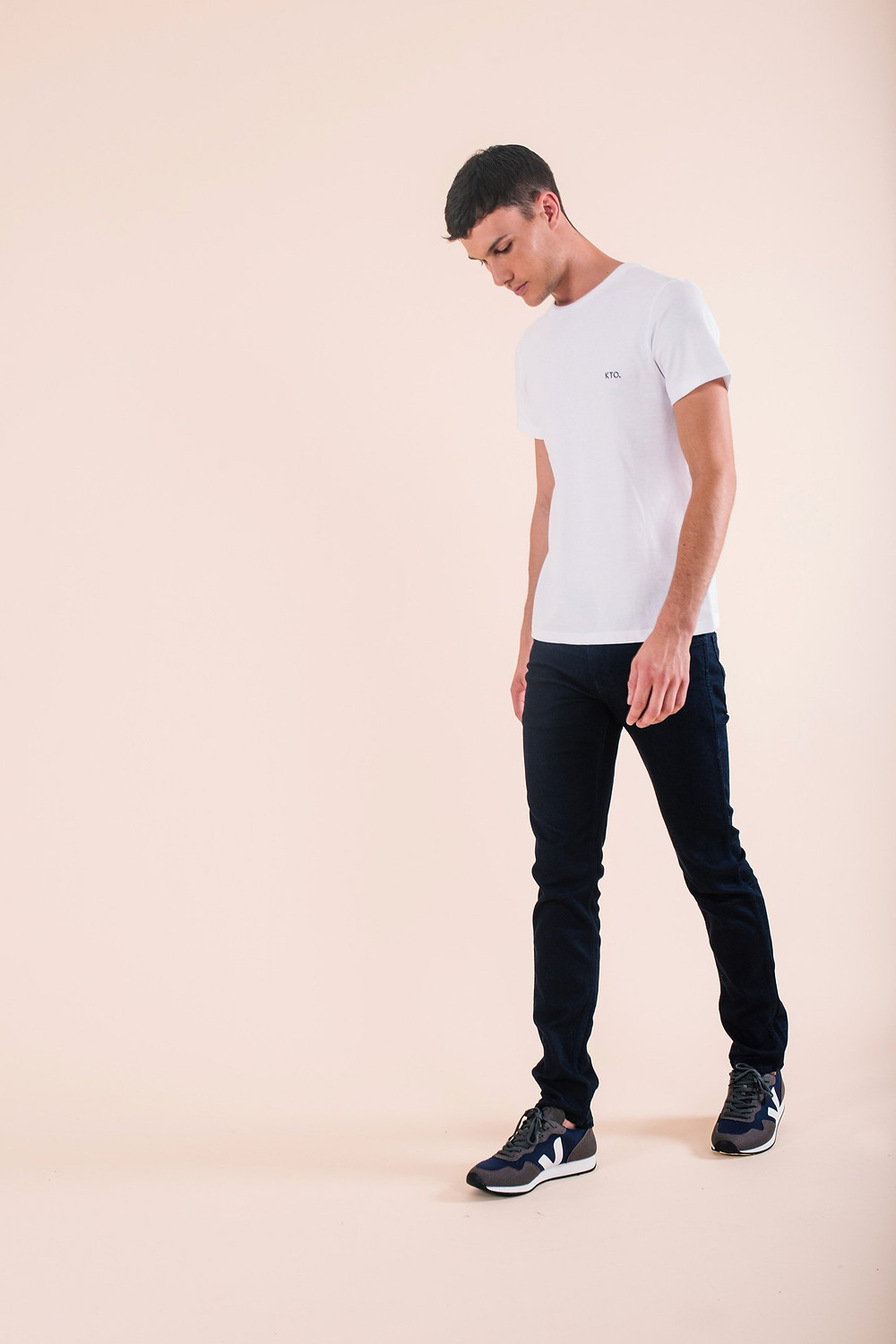 a guy looking down walking in a white t-shirt and black jeans