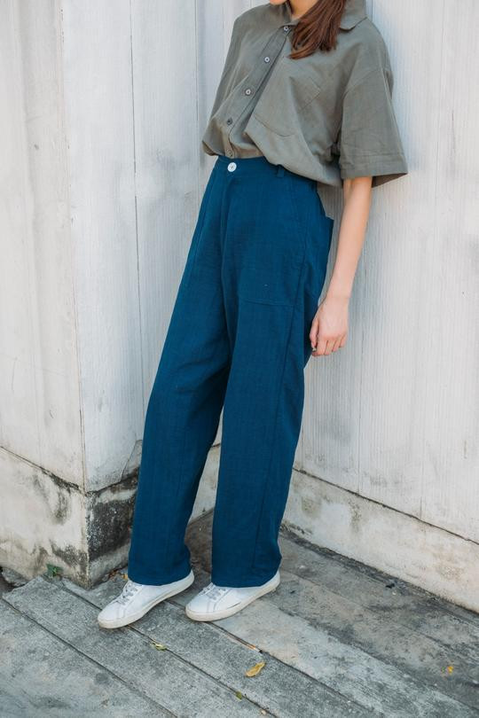 Girl leaning against the wall in indigo trousers and grey shirt ticked in.