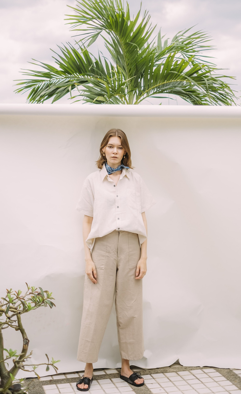 Girl standing against a white wall in a white shirt tucked into the beige wide trousers