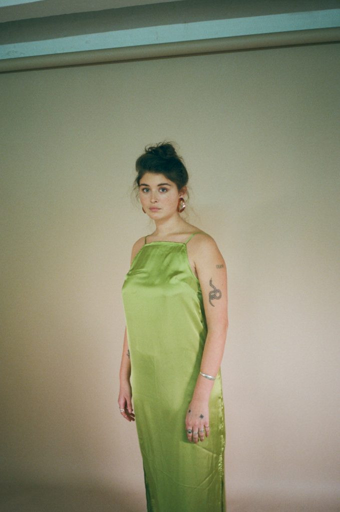 A model in a green silk slip dress with a messy bun