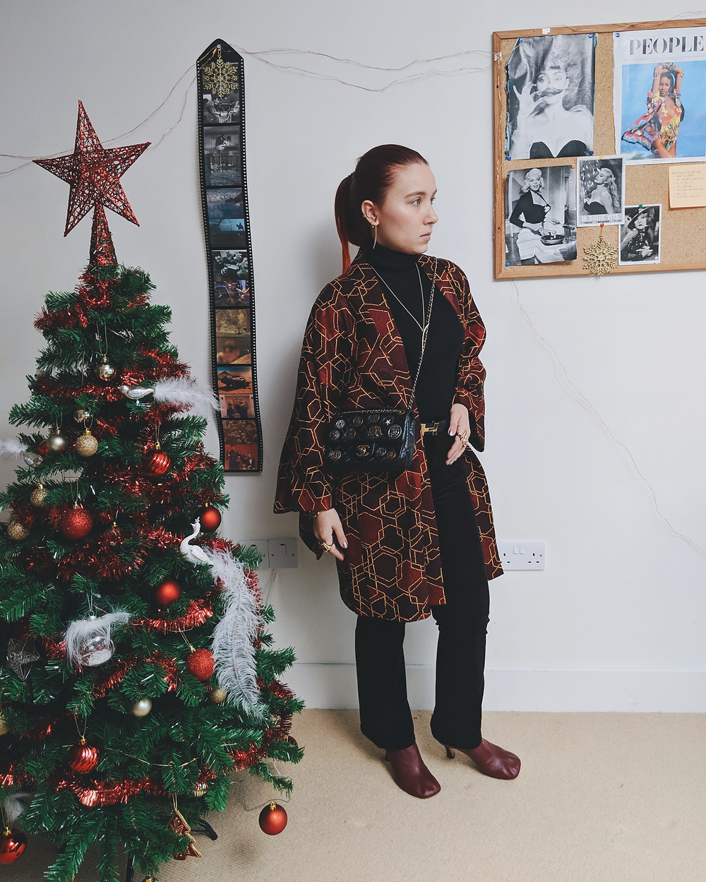 Girl standing against the wall next to a Christmas tree, wearing an open burgundy kimono, lightly flared corduroy black trousers, black rollback. Her hand is on the hip.