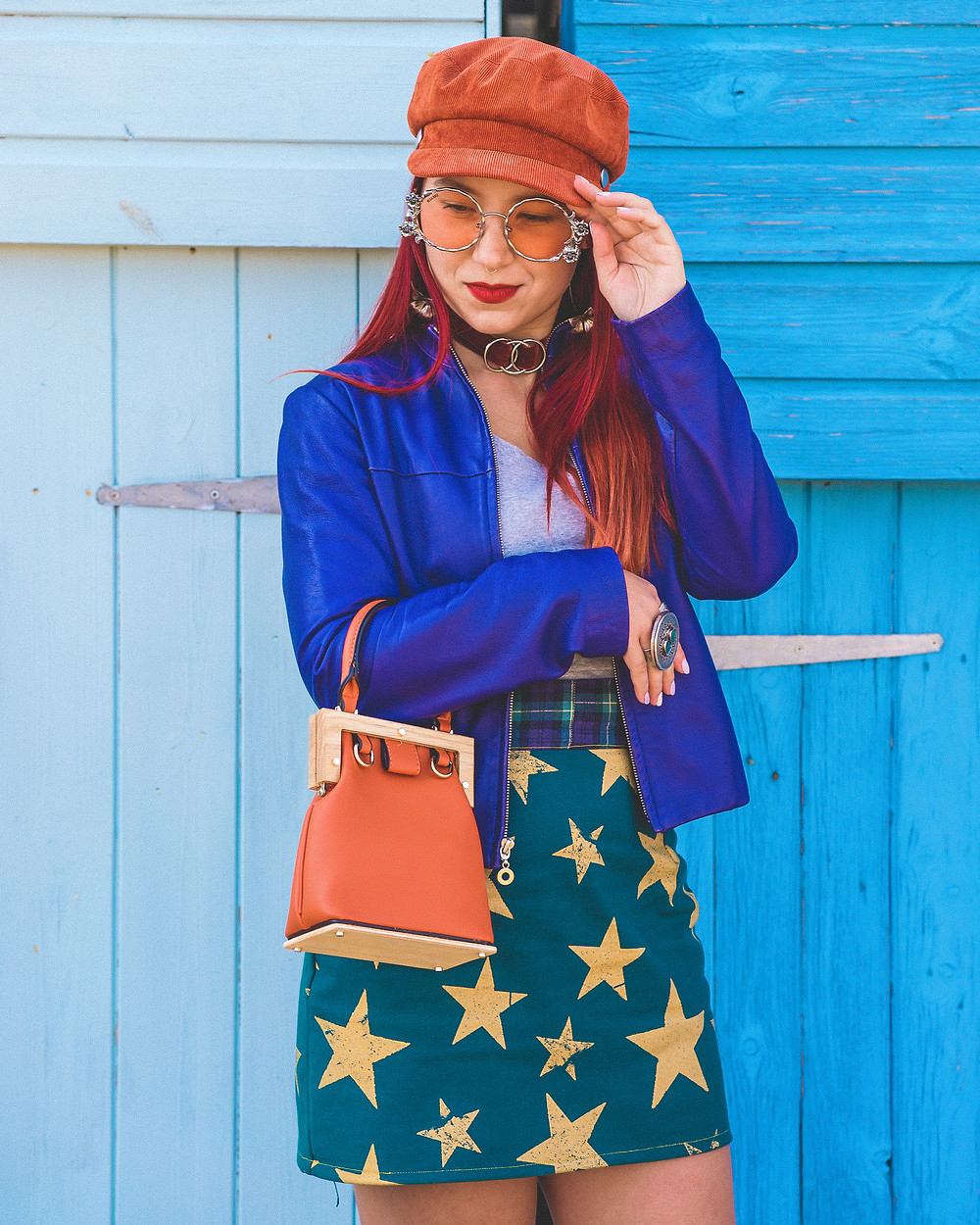 A girl wearing a starry skirt, purple leather jacket and an orange cap.