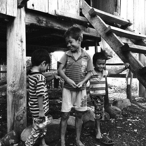 Dos niños de pie en un puente de madera marrón