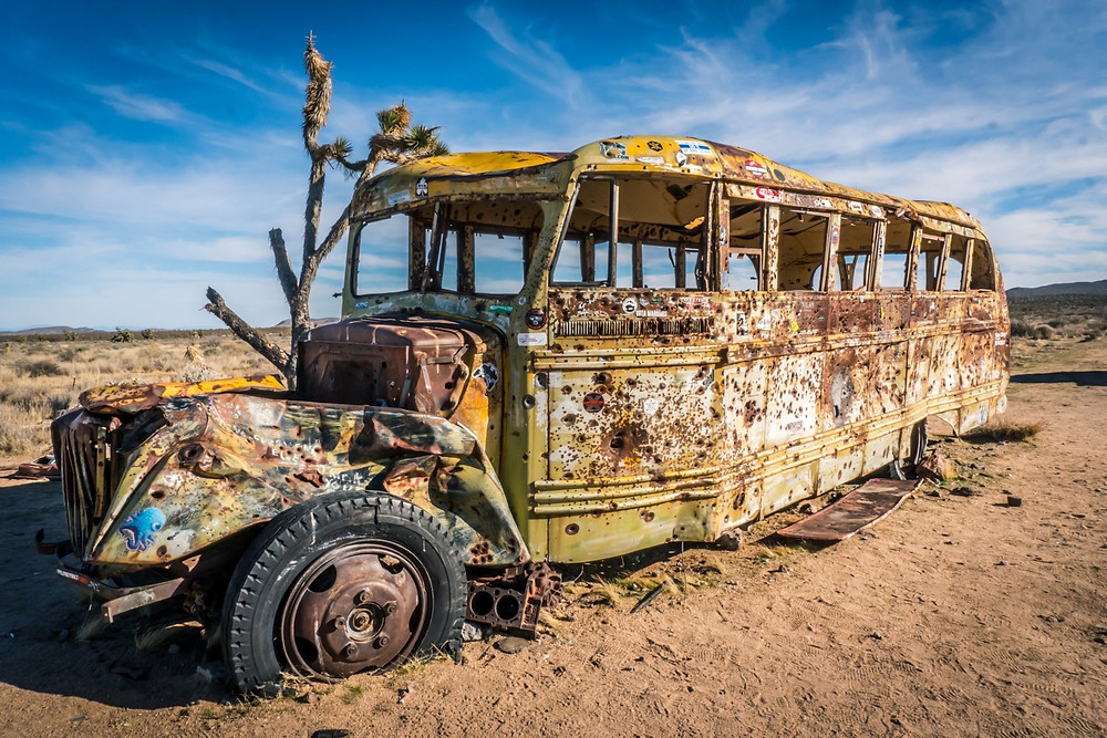 Old beat up rusted school bus abandoned in the desert