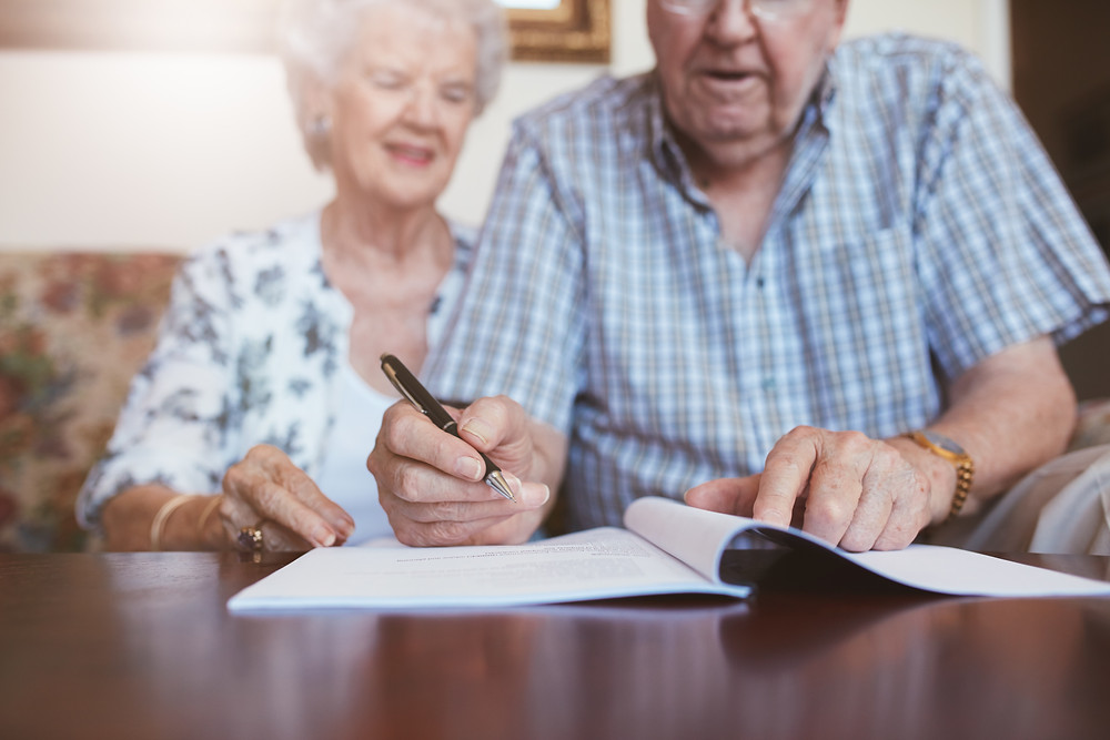 Elderly couple signing Will