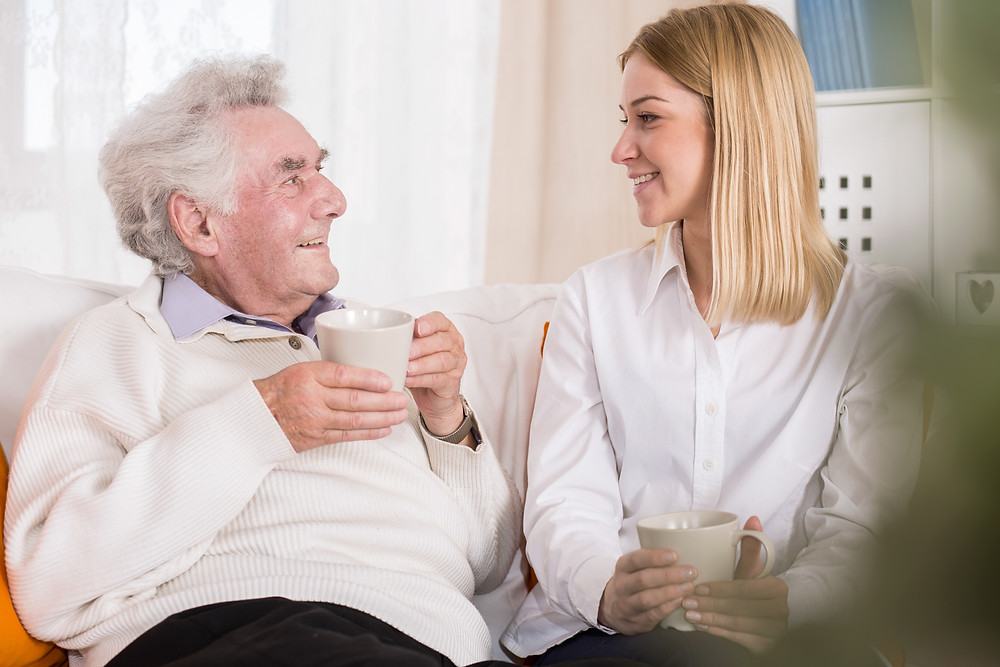 Elderly man talking to young woman