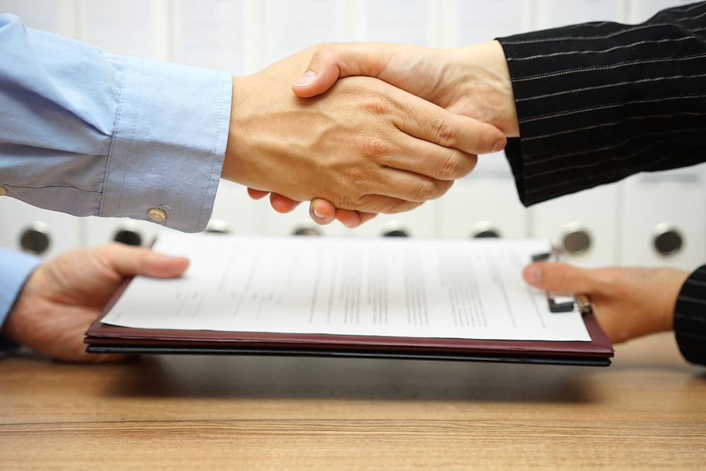 Shaking of hands over signed contract
