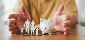 Businessman take a position to protect on the piggybank and paper family in hand, donation