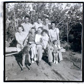 אבא בונדי והבן טומי ישוב על בירכיו, אמא פיני יושבת בקצה השמאלי, בבית החברים, 1943