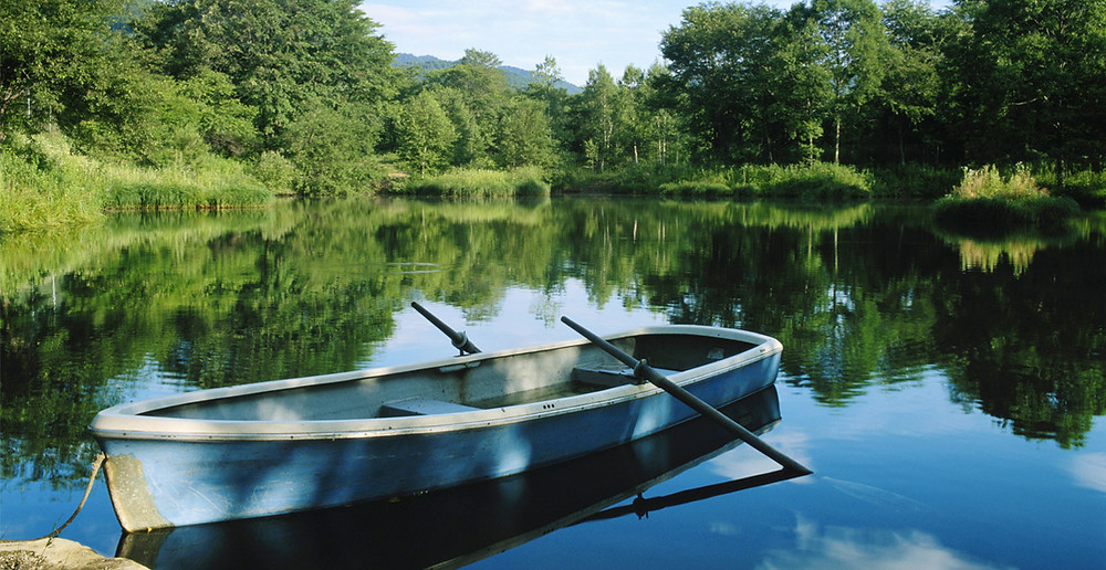 blue canoe on a still pond