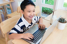 Happy asian boy sitting at his desk With