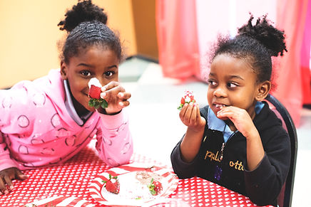 Two young girls smiling with strawberries dipped in yogurt. Photo by Ashley Gibbs