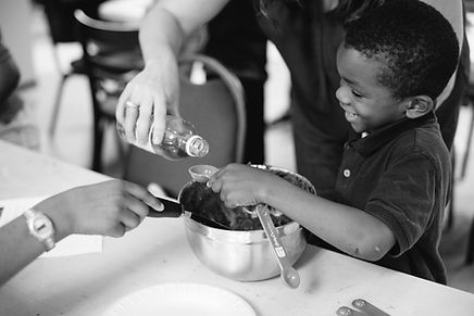 Boy holding measuring spoon and smiling. Photo by Ashley Gibbs