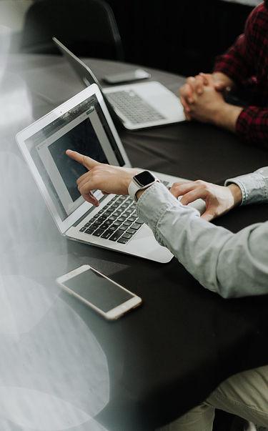To mennesker samarbejder ved bærbar computer.