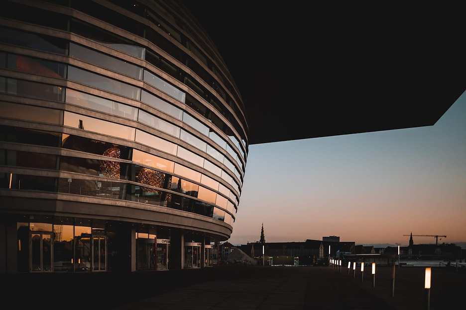Bygning mod havet i solnedgang: erfaringstabel ABA anlæg, teknisk tegning, rådgivning m.m.