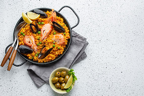 Classic dish of Spain, seafood paella in traditional pan on white wooden background top vi