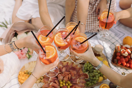 Women toasting with aperol spritz cocktails on summer party. Hen party, event celebration